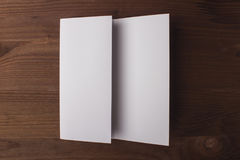 Blank tri fold brochure on wooden background to replace your design or message. Stock Photography