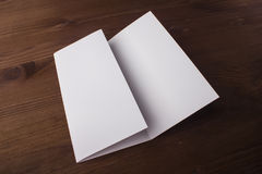 Blank tri fold brochure on wooden background to replace your design or message Stock Photos