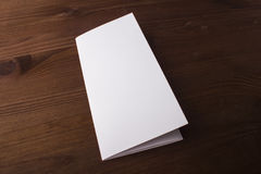 Blank tri fold brochure on wooden background to replace your design or message Stock Photo
