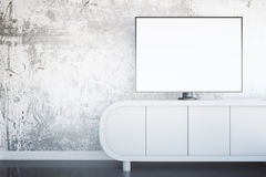 Blank TV screen. Front view of light tv stand with blank white TV screen in interior with textured concrete wall and shiny floor. Mock up, 3D Rendering Stock Photo