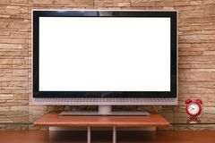 Blank TV set. Modern TV set with empty blank screen and red alarm clock on the table on the decorative brick wall background Stock Photography