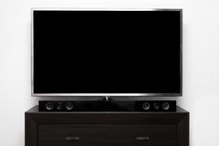 Blank tv with stereo system on brown commode. Against white wall Stock Image