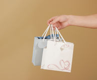 Blank two paper gift bag with hearts mock up holding in hand. Em Royalty Free Stock Photos