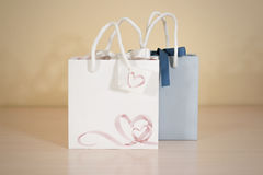 Blank two paper gift bag mock up standing on a wooden table. Emp Royalty Free Stock Photo