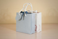 Blank two paper gift bag mock up standing on a wooden table. Emp Royalty Free Stock Image