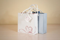 Blank two paper gift bag mock up standing on a wooden table. Emp Stock Photo