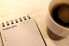 Blank vacation plan list in a A5 sized notebook. And coffee stock photography