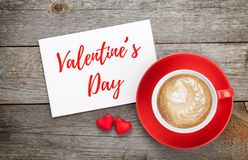 Blank valentines greeting card and red coffee cup. On wooden background Royalty Free Stock Image