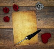 Blank vintage card with red cuddle hart, red roses, ink and quill on vintage oak, love letter on antique oak - top view stock image