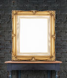Blank vintage golden photo frame lean at black brick wall on woo Royalty Free Stock Image