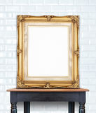 Blank vintage golden photo frame lean at ceramic tile wall on wo Royalty Free Stock Photo