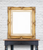 Blank vintage golden photo frame lean at white brick wall on woo Royalty Free Stock Image