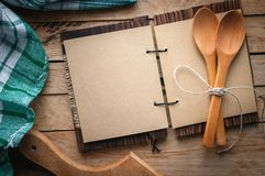 Blank vintage recipe cookbook and utensils on wooden background, copy space royalty free stock images