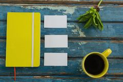 Blank visiting cards, diary, flora and black coffee on wooden plank Royalty Free Stock Photo