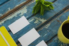 Blank visiting cards, diary, flora and black coffee on wooden plank Royalty Free Stock Image