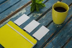 Blank visiting cards, diary, flora and black coffee on wooden plank Stock Photography