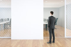 Blank wall in office. Businessman standing in modern office interior with blank white concrete wall and wooden floor. Mock up, 3D Rendering Stock Photography