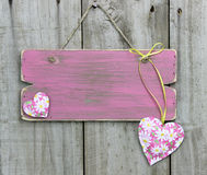 Blank weathered pink sign with flower hearts hanging on wooden door Royalty Free Stock Images