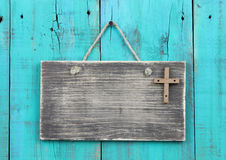 Blank weathered sign with wooden cross hanging by rope on antique teal blue wood door Stock Photography