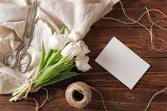 Blank wedding invitation card and bunch of spring flowers on wooden table. White tulips, textile rag, twine, romantic wedding gree. Ting card royalty free stock photography