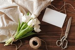 Blank wedding invitation card and bunch of spring flowers on wooden table. White tulips, textile rag, twine, romantic wedding gree. Ting card royalty free stock photos