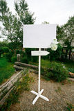 Blank wedding white banner with arrow sign decorated by flowers on stand outdoor. Copy space for your text. Stock Photos