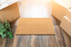 Blank Welcome Mat, Moving Boxes and Plant on Hard Wood Floors Stock Images