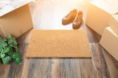 Blank Welcome Mat, Moving Boxes, Shoes and Plant on Hard Wood Fl Stock Photo