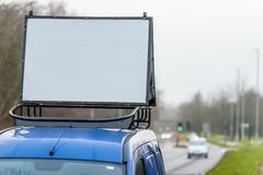 Blank white advertising banner sign on car roof next to UK motorway stock photography
