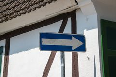 Blank white arrow on blue background street sign on pole with white wall with brown trim in background. Brown roof and green shutt. Ers royalty free stock photography