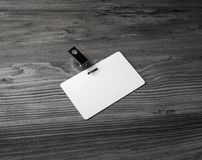 Blank white badge. On wood background. Plastic id card Royalty Free Stock Image