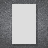 Blank white billboard on black stone wal Stock Image