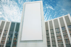 Blank white billboard between business centers with blue sky, mo. Ck up Stock Photography