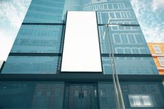 Blank white billboard on glassy wall of business center, mock up Stock Image
