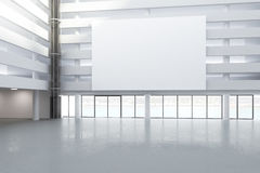 Blank white billboard in the hall of empty building with concret Stock Images