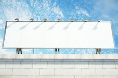 Blank white billboard on the top of building at blue sky backgro Royalty Free Stock Image
