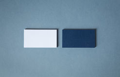 Blank white blue business cards in two stacks. Thick blank double-sided business cards with textured surface stacked up on a grey background Royalty Free Stock Photo