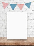 Blank white board and party flags hanging on white brick wall ba Royalty Free Stock Images