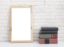 Blank white board and stack of books on table Royalty Free Stock Image