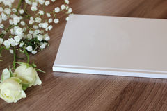 Blank white book, journal, wedding guestbook, notebook mockup. Object for design and branding. White flowers and wooden texture, perspective view royalty free stock image