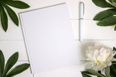 Blank white book, journal, wedding guestbook, notebook mockup. Object for design and branding. White peony and wooden texture, top view stock image