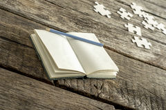 Blank white book with pencil and puzzle pieces Royalty Free Stock Images