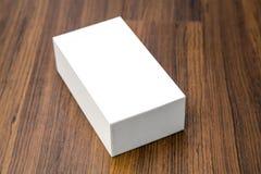 Blank white box mock up. On wood background Royalty Free Stock Photo