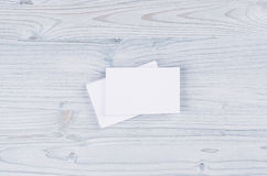Blank white business card on soft light blue wooden board. Mock up for branding identity. Stock Photos