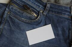 Blank white business card on top of blue jeans