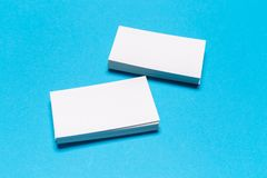 Blank white business cards on blue background. Mockup for branding identity stock images