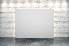 Blank white canvas in the center of white brick wall. With concrete floor Royalty Free Stock Image