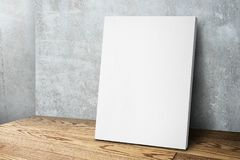 Blank white canvas frame leaning at concrete wall and wood floor. Mock up template for adding your design royalty free stock images