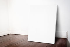 Blank white canvas frame leaning at grunge house wall and dark b Stock Image