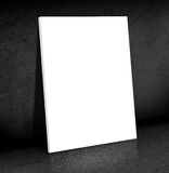 Blank white Canvas poster leaning at black cement room, Mock up Royalty Free Stock Photography